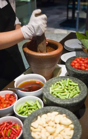 pounding: Cook is pounding ingredients in order to make Green Papaya Salad