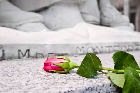 Rose laying at the bottom of monument as for commemoration Stock Photo