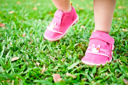 Baby taking her small steps on green grass