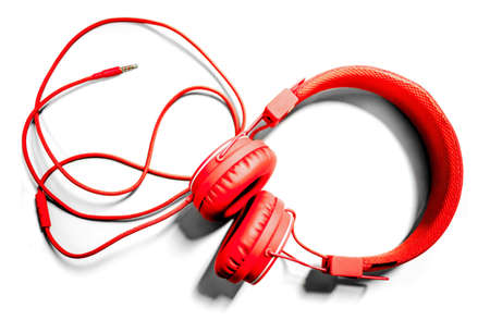 Red headphones with long wire isolated on white