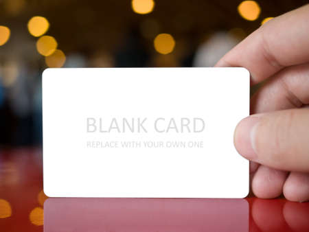 Hand holding white dummy card (to be replaced with your own) in the elegance atmosphere