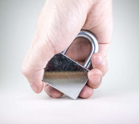 Hand holding the used, scratchy, silver padlock isolated on white