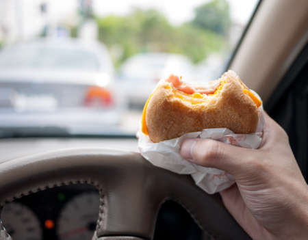urban life: Conductor de comer hamburguesa en el coche ya que el tr�fico es muy malo en la ma�ana. Resumen de la vida urbana.