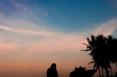 silhouette woman relaxing on the sunset beach view with beach chair and coconut tree in scene Stock Photo