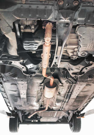 rusty car: Standard car exhaust system in orange color. Shot from under the car.