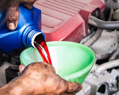 Mano vertiendo l�quido de la transmisi�n a trav�s de embudo que para el buen mantenimiento del coche