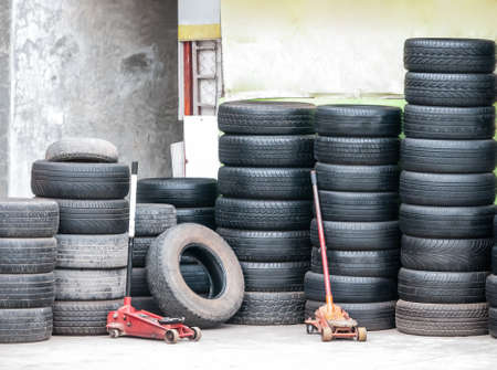 Stacks of used car tires and hydraulic floor jack. Symbolize of used car tires recycle business. Stock Photo