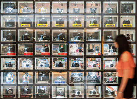 Bangkok, Thailand - May 1, 2013 - Women is looking at the digital cameras laying on glass shelf. The high quality mirrorless camera is gaining more market share nowadays.
