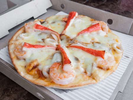 Seafood pizza delivered in the paper box Stock Photo