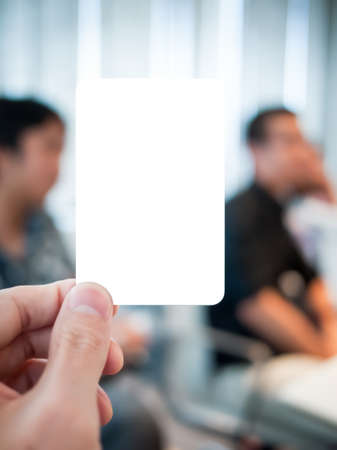 Hand holding card in the serious meeting. Able to put any message in there such as