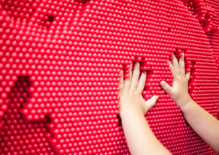 Playful baby hands making handprint on the red pin toy. Abstract of fun playing. Stock Photo