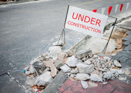 Under construction notice on the roadside to warn every walking people Stock Photo