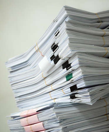 managed: Pile of documents stack up high waiting to be managed Stock Photo