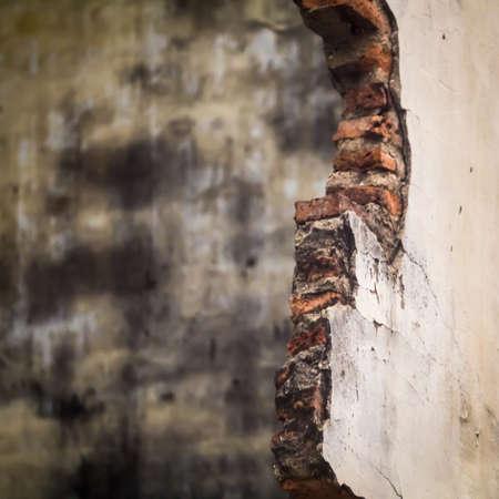 Damaged wall showing bricks with grunge background
