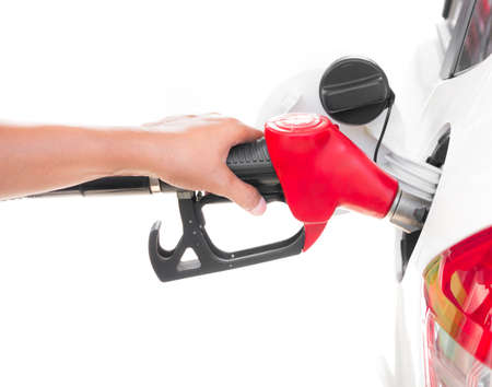 Hand holding gasoline nozzle filling up the white car isolated on white background