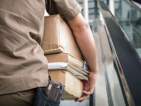 cartero: Cartero que lleven paquetes en la mano para entregarlos al cliente Foto de archivo