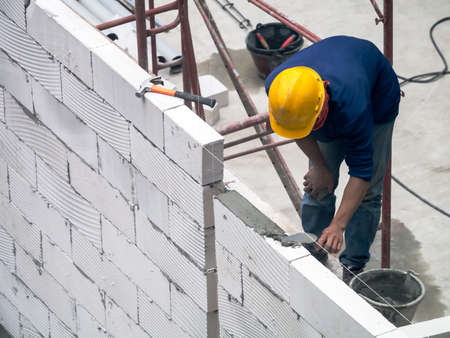 Construction worker is building a wall using autoclaved aerated concrete blocks
