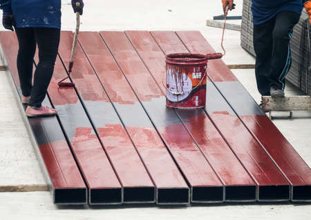 rustproof: Worker painting iron bar with the rust-proof color in the construction area