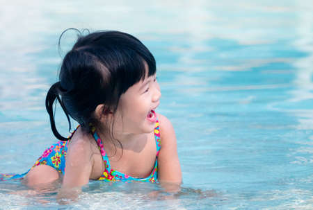 Happy asian kid laugh while playing in the swimming pool photo
