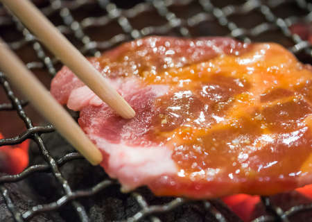 Grill pork on hot charcoal using chopstick photo
