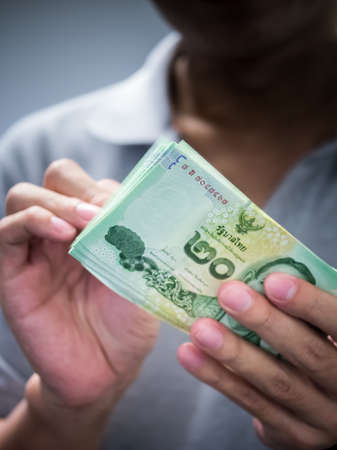 Man holding banknote in low key abstract of illegal money offering