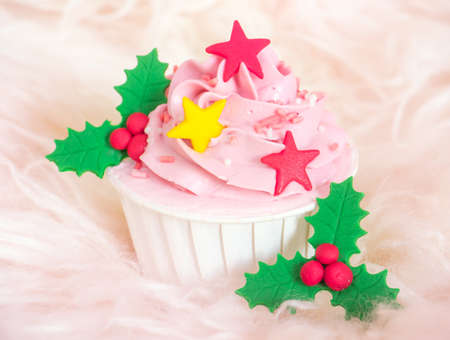 Sweet pink cupcake with stars and holly berry decorated on soft fur background Stock Photo