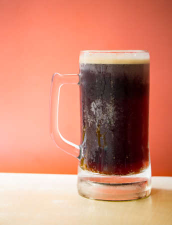 root beer: Cold root beer on top of wooden table in front of orange background
