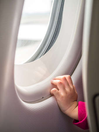 Child hand touching airplane window in concept of the first flight