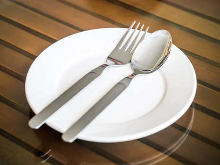 Empty plate with spoon and fork on the glass top wooden table