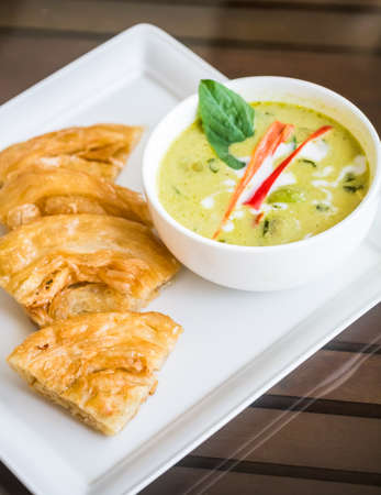 Green curry chicken soup with nan, an Indian-Thai fusion food, on glass top wooden table Stock Photo