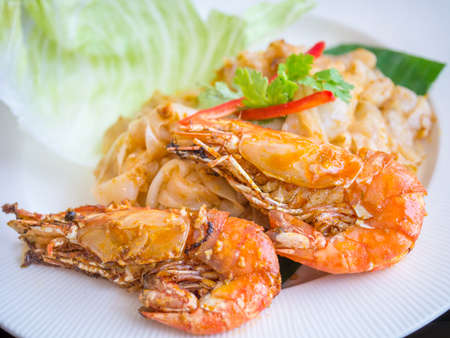 Fried noodle with prawn served on white plate
