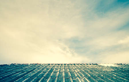 Cloudy sky over the asbestos roof tiles processed in vintage style able to use as background