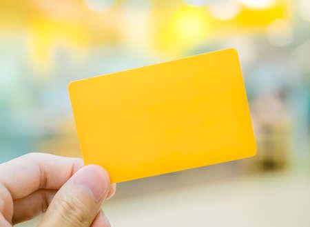 エレガントな雰囲気の中で黄色のダミー カード (置き換えられますあなた自身) を持っている手