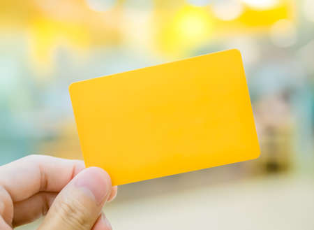 Hand holding yellow dummy card (to be replaced with your own) in the elegance atmosphere photo