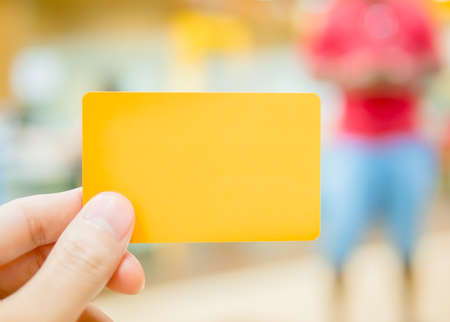 Hand holding yellow dummy card (to be replaced with your own) with a man in red and blue costume in the back Stock Photo