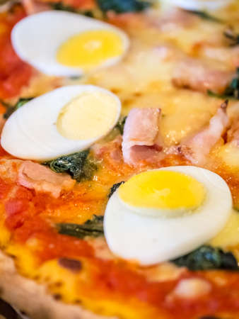 Closeup shot of boiled egg topped homemade pizza Stock Photo