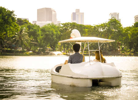 Love couple relaxing in the park rowing boat together processed in golden color Stock Photo