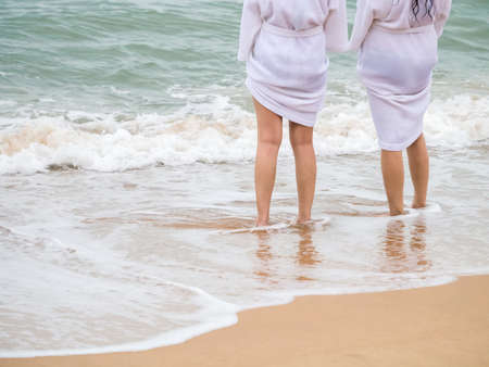 Women legs standing on the beach wearing white rope relaxing the summer trip