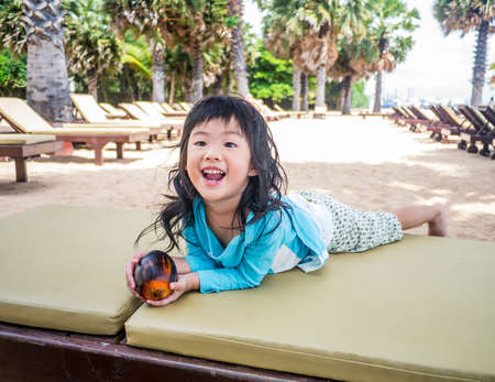 Happy asian girl smiling while enjoy travelling to the beach