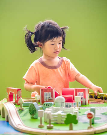 Asian child girl playing wooden train on green background