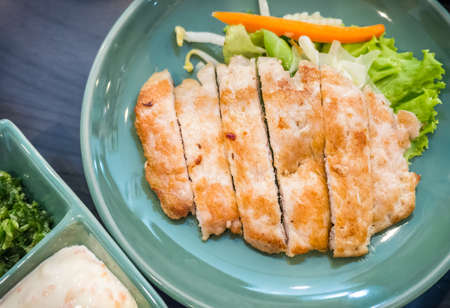 Cut pork steak served in the green plate with dipping sauce Stock Photo