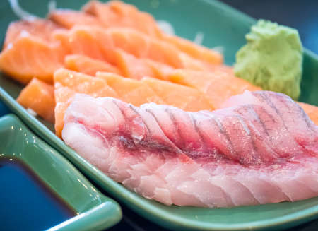 Various juicy raw fish put into green plate shot on dark background Stock Photo
