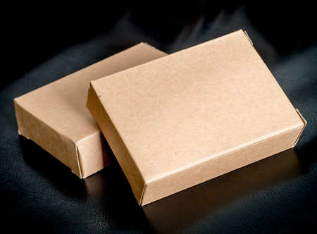 cardboard box: Two blank recycled paper boxes on black leather background