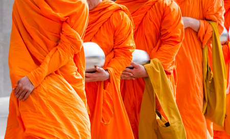 Buddhist monks holding silver buddhist alms bowl in hand walking together in the morning