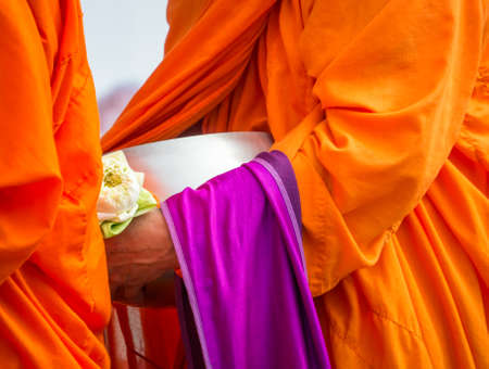 Buddhist monk holding alms bowl and lotus flower in religious concept Stock Photo