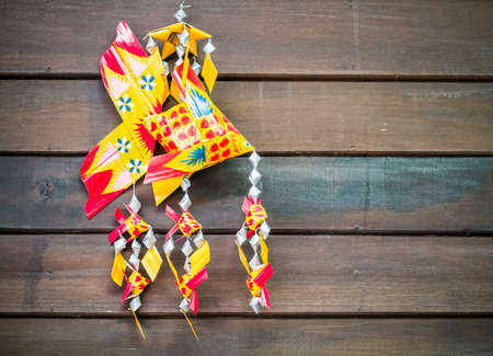 Handmade carp wicker mobile hanging in front of wooden background Stock Photo