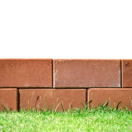 Brick layers on green grass leaving white space on top