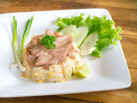Closeup of fried rice with pork served in square dish on wooden tabletop