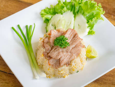 Closeup of fried rice with pork served in square dish on wooden tabletop Stock Photo - 43049294