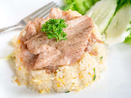Closeup of fried rice with pork in white dish